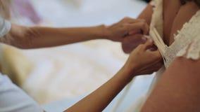 Невеста утра Bridesmaid связывая смычок на платье свадьбы Руки ` s женщины шнуруют вверх silk ленту на корсете ` s невесты Помога сток-видео