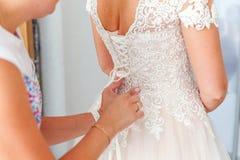 Невеста Bridesmaid помогая прикрепить шнуровать ее платье свадьбы белое перед церемонией стоковое фото