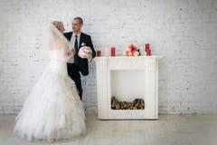 невеста groom на их день свадьбы около камина Стоковое Изображение