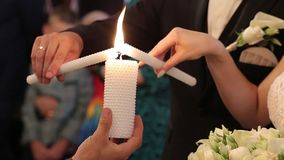 Невесты освещают свечу preists в церков на свадебной церемонии акции видеоматериалы