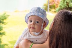 Невиновный портрет стороны младенца в шляпе солнца над плечом матери на bakcground природы стоковые изображения