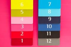 12 дневников другого цвета на розовом деревянном столе Стоковые Изображения RF