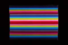 12 дневников другого цвета на черном стеклянном столе Стоковая Фотография RF