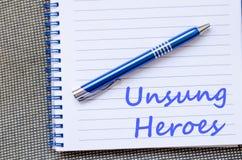 Невоспетые герои пишут на тетради Стоковое Фото