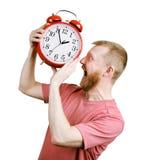Негодует бородатый человек хочет съесть будильник стоковое изображение