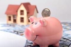 Недвижимость или домашние сбережения копилка с монетками на деньгах и доме предпосылки нерезкости Стоковые Изображения