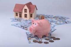 Недвижимость или домашние сбережения копилка с монетками на деньгах и доме предпосылки нерезкости Стоковое Изображение RF