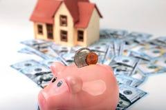 Недвижимость или домашние сбережения копилка с монетками на деньгах и доме предпосылки нерезкости Стоковые Фото