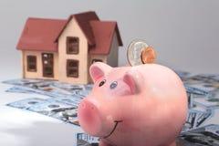 Недвижимость или домашние сбережения копилка с монетками на деньгах и доме предпосылки нерезкости Стоковая Фотография