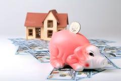 Недвижимость или домашние сбережения копилка с монетками на деньгах и доме предпосылки нерезкости Стоковое Фото