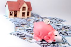Недвижимость или домашние сбережения копилка с монетками на деньгах и доме предпосылки нерезкости Стоковое Изображение
