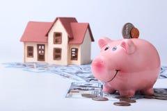Недвижимость или домашние сбережения копилка с монетками на деньгах и доме предпосылки нерезкости стоковые фотографии rf