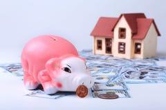 Недвижимость или домашние сбережения копилка с монетками на деньгах и доме предпосылки нерезкости стоковые изображения rf