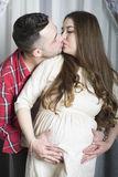 Нежная поцелу-счастливая пара ожидая рождения их ребенка Стоковое фото RF