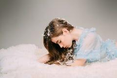 Нежность и хрупкость концепции молодости Девочка-подросток взгляда со стороны лежа на дремотной кровати на серой предпосылке крас стоковое изображение
