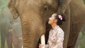 Нежность молодой привлекательной азиатской женщины в традиционном костюме со слоном видеоматериал