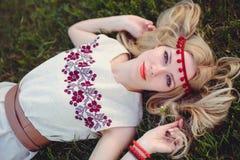 Нежные белокурые лож женщины на траве одели в естественной вышитой повязке платья на ее голове, на зеленой предпосылки стильное Стоковые Фотографии RF