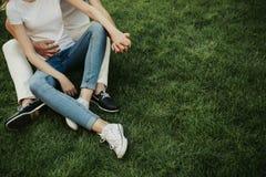 Нежные действующие пары размещая на зеленой траве стоковая фотография rf