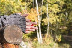 Нежные женские руки при маникюр, подпиранный на деревянных перилах Стоковое Фото