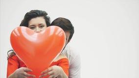 Нежные пары красота девушки и ее красивого парня, держащ сердце в форме воздушных шаров и поцелуев Счастливый видеоматериал