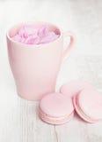 Нежные розовые macaroons и чашка чая на белой деревянной предпосылке Стоковые Изображения