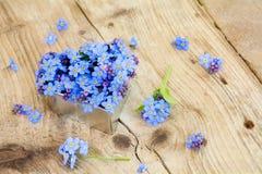Незабудка цветет в серебряной форме сердца на деревенской древесине Стоковое Фото