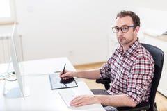 Независимый график-дизайнер работая на его компьютере стоковое изображение rf