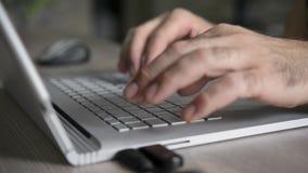 Независимый работник печатает и работает на компьтер-книжке акции видеоматериалы