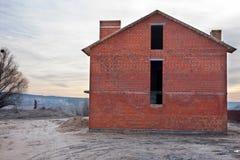Незаконченная конструкция дома кирпича, все еще под конструкцией Незаконченная крыша под конструкцией Стоковое Фото