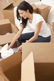 Незамужняя женщина распаковывая коробки двигая дом Стоковые Изображения RF