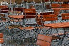 Незанятые стулья и таблицы в ресторане сада при ноги таблицы и ноги стула сделанные железных и деревянных верхних частей Стоковые Фото