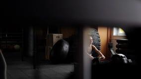 Незнакомец шпионя по мере того как атлетическая девушка выполняет тренировки с имитатором силы акции видеоматериалы