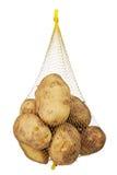 Незрелые органические картошки в сумке сетки изолированной на белой предпосылке Стоковые Фото