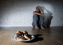 Нездоровые donuts сахара и булочки и уговоренная девушка молодой женщины или подростка сидя на земле Стоковая Фотография