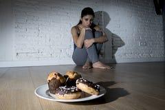Нездоровые donuts сахара и булочки и уговоренная девушка молодой женщины или подростка сидя на земле Стоковые Изображения