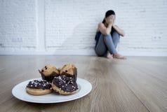 Нездоровые donuts сахара и булочки и уговоренная девушка молодой женщины или подростка сидя на земле Стоковые Фото
