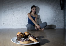 Нездоровые donuts сахара и булочки и уговоренная девушка молодой женщины или подростка сидя на земле Стоковое Изображение