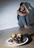 Нездоровые donuts сахара и булочки и уговоренная девушка молодой женщины или подростка сидя на земле Стоковые Изображения RF