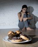 Нездоровые donuts сахара и булочки и уговоренные молодая женщина или te Стоковая Фотография