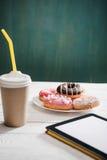 Нездоровый завтрак с кофе, который нужно пойти, плитой замороженных donuts и цифровым экраном белизны таблетки Стоковые Фото