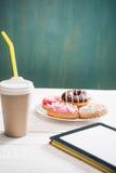Нездоровый завтрак с кофе, который нужно пойти, плитой замороженных donuts и цифровой таблеткой с белым экраном на деревянном сто Стоковое фото RF