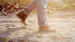 Неизвестная персона идя вдоль пылевоздушной дороги Поднимающее вверх ноги близкое акции видеоматериалы