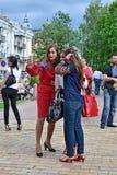 Неизвестные молодые женщины в национальных костюмах делают durin selfie Стоковая Фотография RF