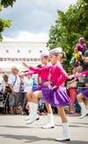 Неизвестные младшие majorettes в розовых и фиолетовых костюмах с жезлами Стоковые Фотографии RF