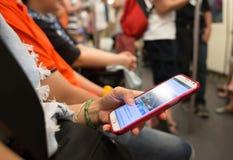 Неизвестные люди используют мобильный телефон пока перемещение метро Стоковая Фотография