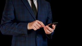 Неизвестный бизнесмен в костюме на черной предпосылке Человек держит смартфон и касается экрану телефона с пальцем сток-видео
