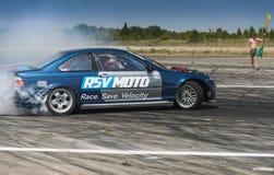 Неизвестный всадник на BMW бренда автомобиля совершает ошибка на trac Стоковые Фотографии RF