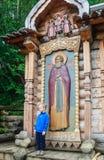 Неизвестный мальчик около малой часовни около источника святой воды Стоковое Изображение