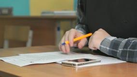 Неизвестный студент пишет текст используя ручку в тетради сток-видео