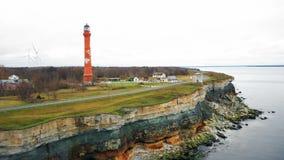 Неимоверная воздушная готовя съемка красивого выветренного берега моря с изумлять старые маяк и здания в поле осени сток-видео